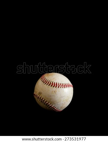 A worn baseball sits alone on a solid black background.