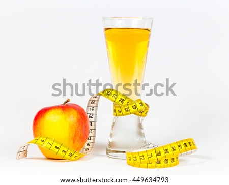 A yellow measuring tape wrapping red apple and juice - healthy eating concept