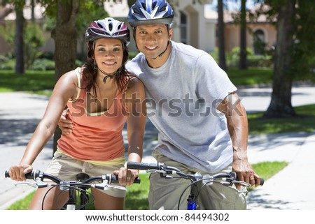 A young African American woman & man couple riding bicycles in the summer