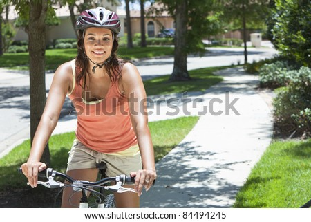 A young African American woman riding bicycle in the summer