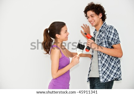 A young and attractive couple holding a paintbrush and an electric screwdriver