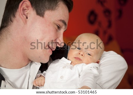 a young and happy father admiring his 7 weeks old daughter