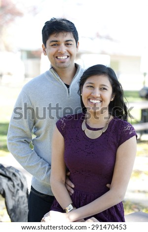A young and happy Indian couple posing on a picnic bench on a sunny day.