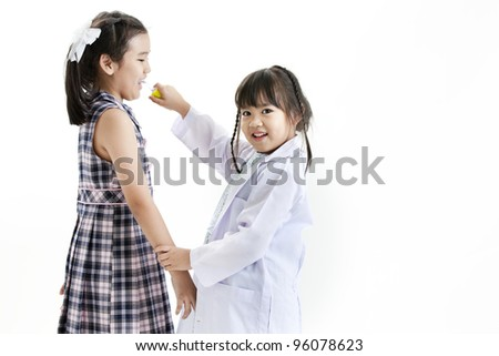 A young asian girl having fun playing dress up as a dentist