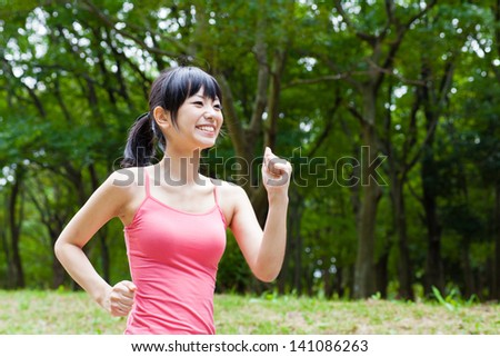a young asian woman jogging in the park