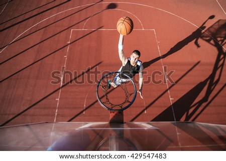 A young basketball player scoring a slam dunk.