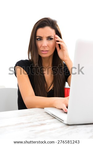 A young beautiful woman being disgusted by content found on the internet using a Laptop computer at home.
