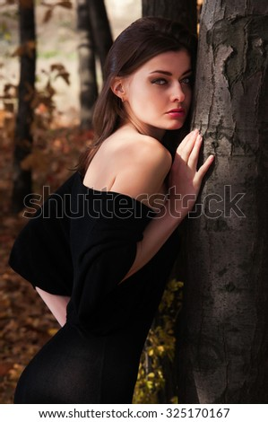A young beautiful woman out alone in the autumn forest