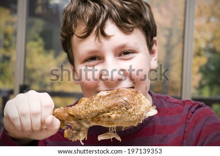 A young boy eating a cooked turkey drumstick.