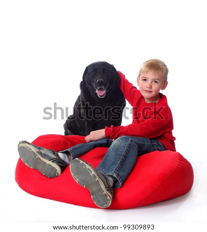 A young boy in red, on a red bean bag chair, with his arm around a black lab.