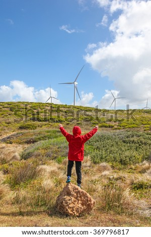 A young boy standing in front of coastal landscape with wind turbines in the background on the southern coast of Victoria - Australia.