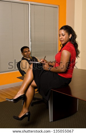 A young business professional with a cigar in his mouth is checking out his secretary's legs as she takes notes.