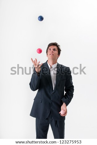 A young businessman deftly juggles three colored balls in front of a white background
