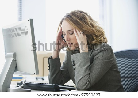 A young businesswoman is looking stressed as she works at her computer. Horizontal shot.