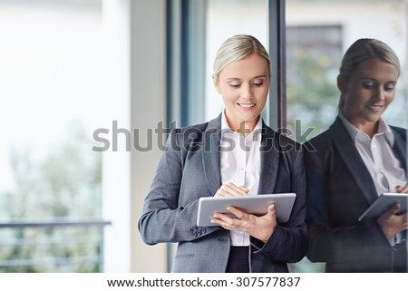 A young businesswoman working on her tablet outdoors
