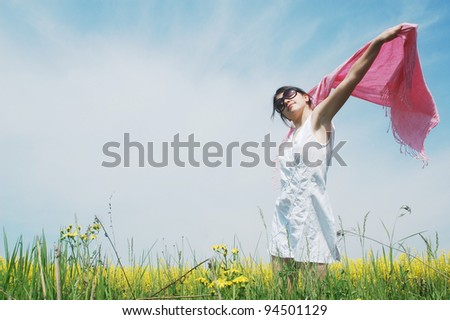 A young caucasian woman enjoying a sunny day on a field of spring flowers.