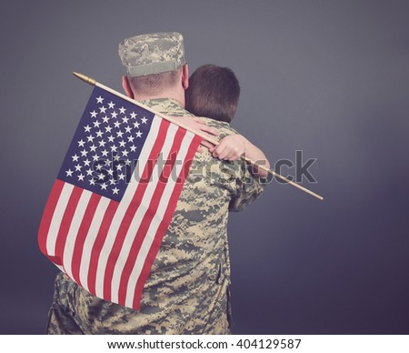 A young child is hugging his army soldier father and holding a usa flag. The child and dad are isolated on a blue background for a patriot or family concept.