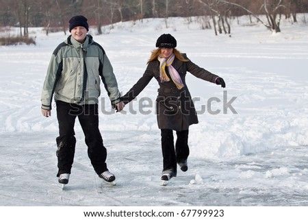 A young couple enjoys a leisurely skate in winter.