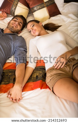 A young couple holding hands while lying on the bed in a asian style hotel room.