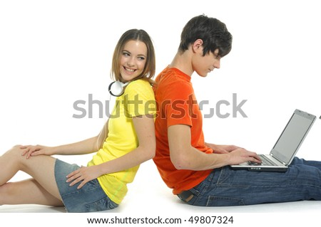 A young couple using a laptop computer back to back