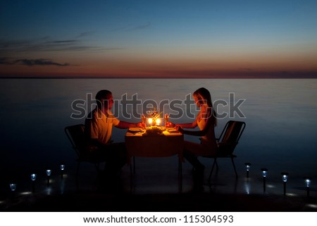 A young couple with a romantic dinner with candles on the sea sand beach