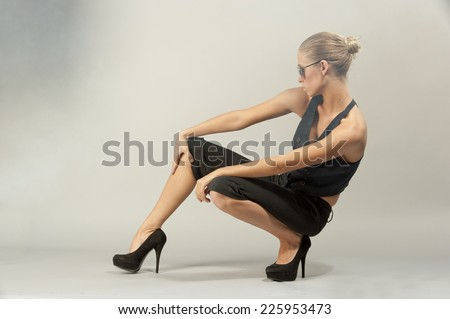 A young female model crouching on a gray background in a studio setting while wearing sunglasses and a black outfit.