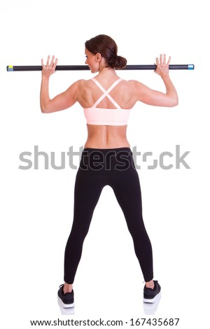A young fit woman wearing a cute exercise outfit using an exercise bar.