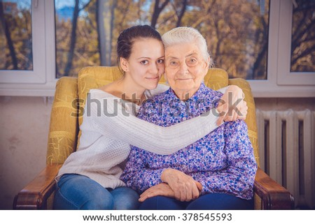 A young girl and an elderly grandmother. Girl hugging her grandmother.
