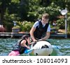 A young girl climbing onto a float, helped by a preteen boy, getting ready to be pulled by the boat. - stock photo