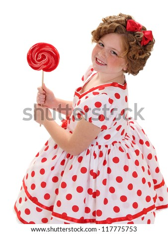 A young girl holds a red lollipop isolated on white
