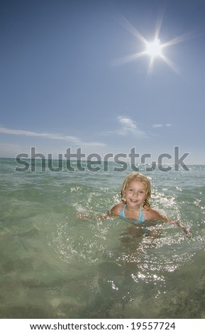 a young girl plays in the ocean on a calm bright sunny day