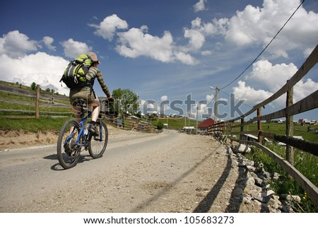 A young girl riding a mountain bike outdoor, in a village area