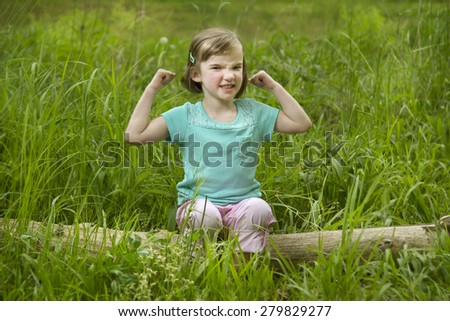A young girl sitting on a log outside in the grass. She is flexing her arms and making a tough expression. Horizontal.