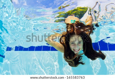 A young girls shows her face underwater