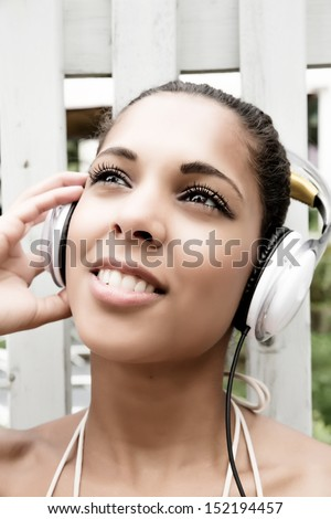 A young hispanic girl enjoying music outdoor.
