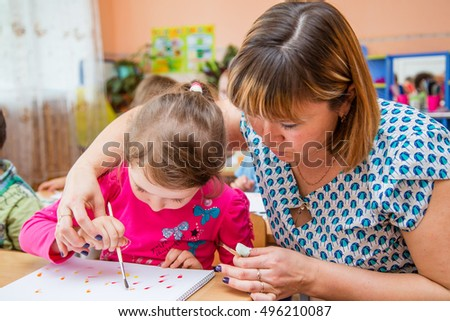 a young kindergarten teacher teaches kids how to draw helps to keep the brush for drawing