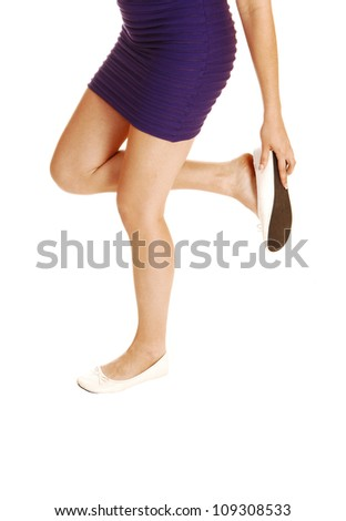 A young lovely woman fixing her shoe, standing from the front for white background, looking down to her shoe, in a short lilac dress.