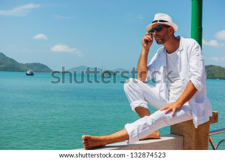 A young man in a white suit sits on the waterfront