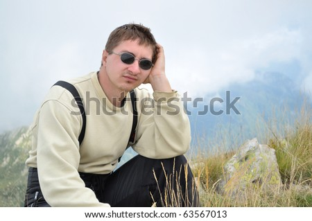 A young man sits on a hilltop and looking thoughtfully into the distance