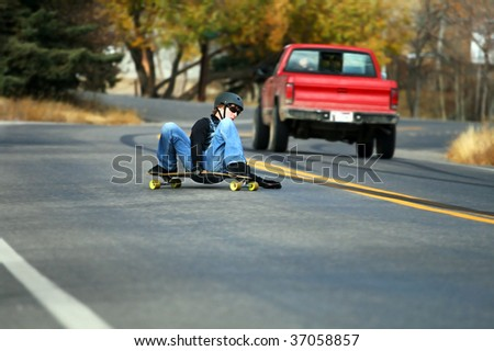 A young man skateboards past a truck on a steep residential road.