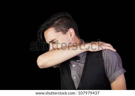 young man sneezing into his elbow. Black background. - stock photo