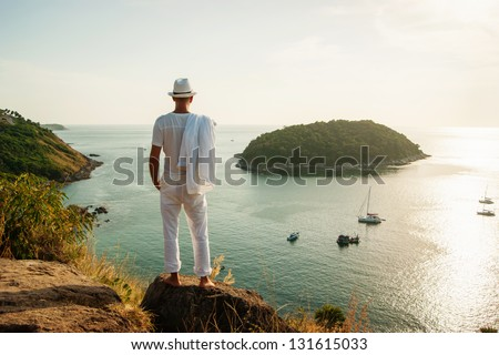 A young man standing on a rock and looking at the sunset of Phuket