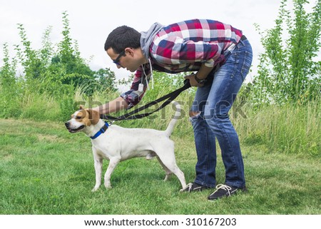 A young man trains a medium sized dog.