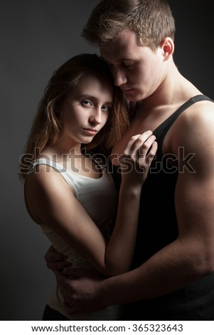 A young man with beautiful girl in the studio on gray background