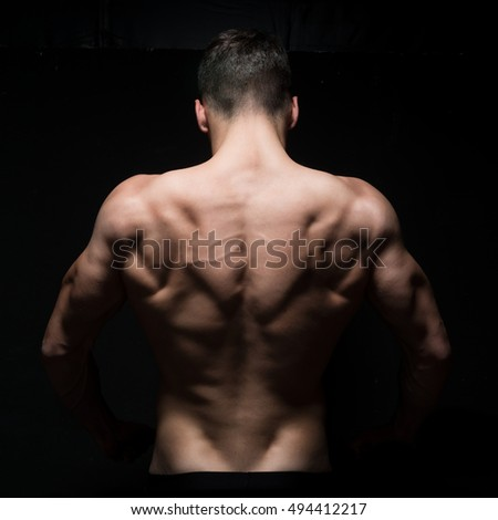 A young muscular athlete man, back view