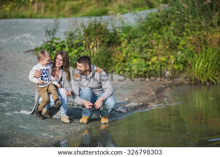 A young parents with their son sit on a coast