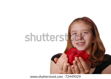 A Young Red Head Holds a Handful of Red Rose Petals, Selective Focus on Face, Isolated on White with Room for Text