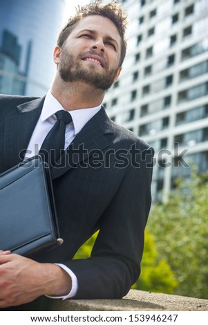 A young successful man, male executive businessman relaxing in front of a high rise office block in a modern city