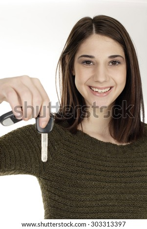 A young woman hands a car key to viewer. Focus is on face.