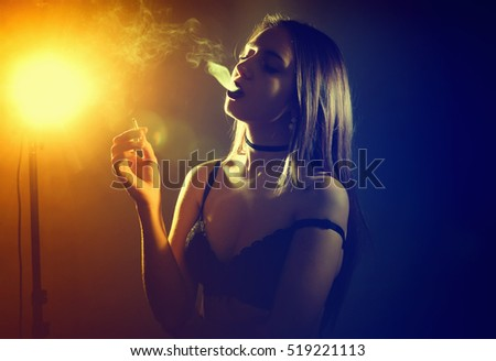 A young woman in lingerie with a cigarette blows smoke from her mouth